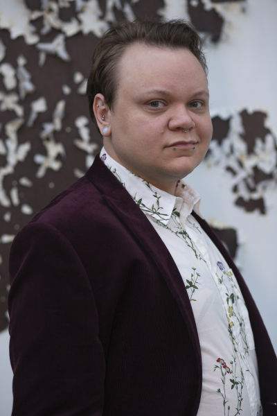 Photograph of the artist in a burgundy velvet sport coat and floral button down.